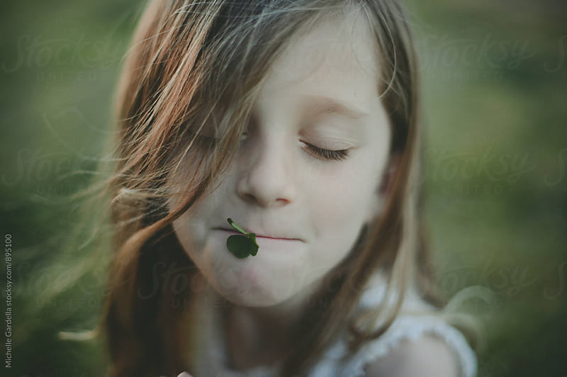 Girl with a clover in her lips by Michelle Gardella for Stocksy United