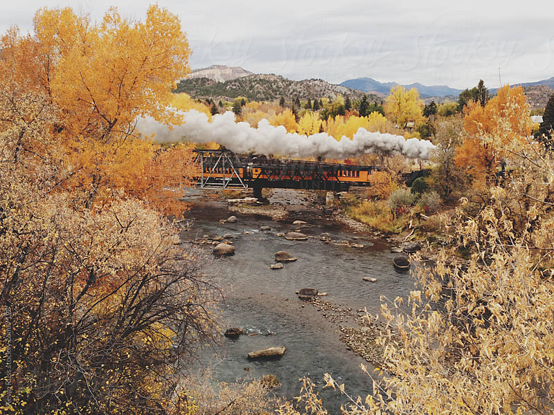 Fall Steam Train Crossing River on Bridge by Kevin Russ for Stocksy United