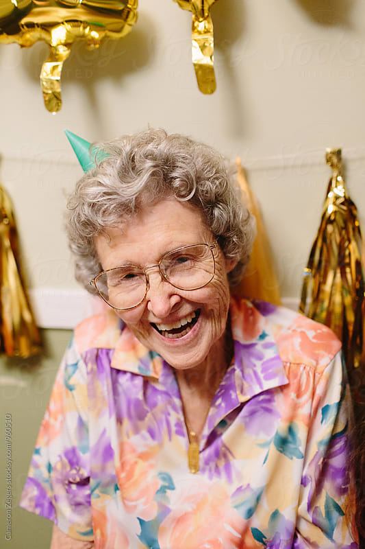 elderly woman smiling wearing birthday hat by Cameron Zegers for Stocksy United
