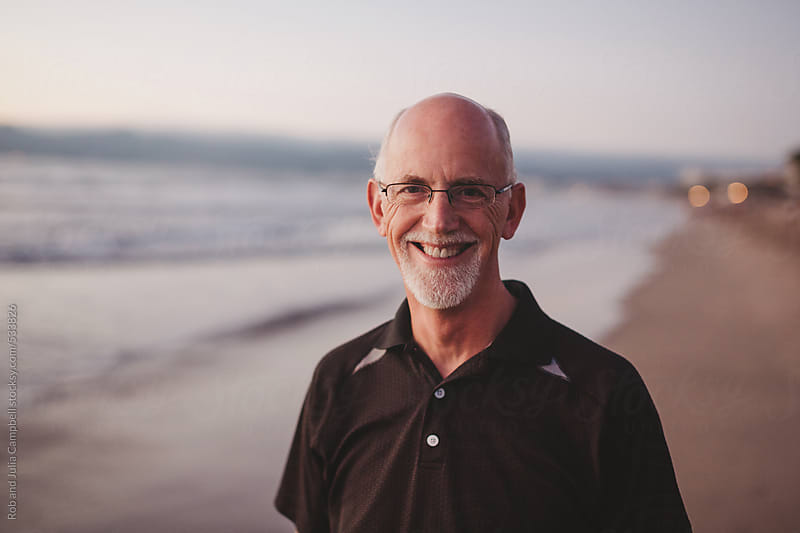 Happy middle aged, retired man smiling outside on ocean beach at sunset by Rob and Julia Campbell for Stocksy United