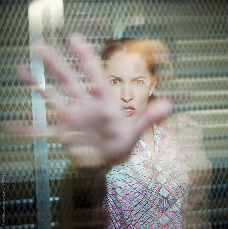 Angry young woman reaching towards camera by Paul Edmondson for Stocksy United