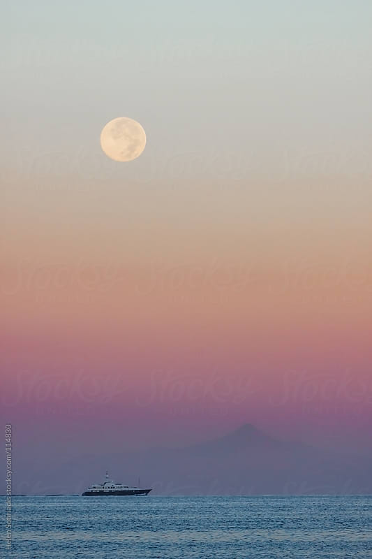 The Full Moon over a Boat in the Sea, at Sunset by Helen Sotiriadis for Stocksy United