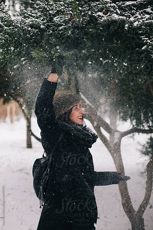 Happy woman having fun in the park on a snowy day by Marija Mandic for Stocksy United