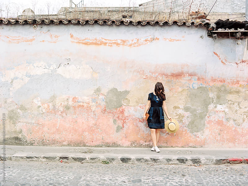 Woman standing in front of colorful wall by Daniel Kim Photography for Stocksy United