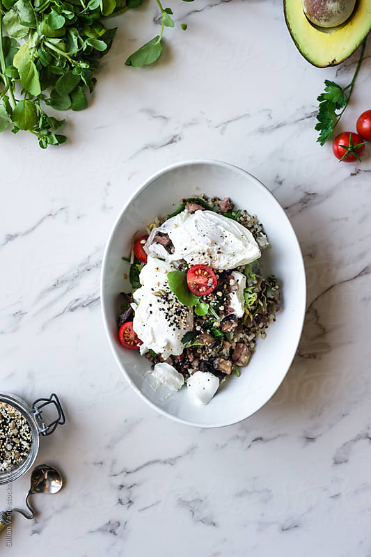 breakfast salad with greens, quinoa, poached eggs, avocado, goat by Gillian Vann for Stocksy United