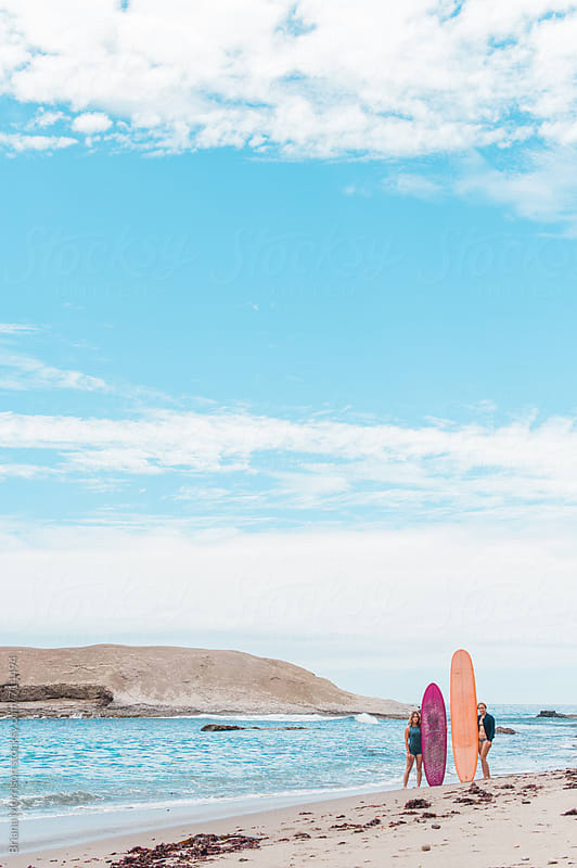Two Female Surfers Standing on the Beach with their Surfboards by Briana Morrison for Stocksy United