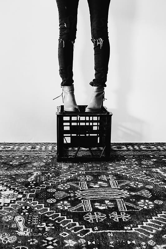 Legs of woman standing on plastic milk crate indoors by Jacqui Miller for Stocksy United