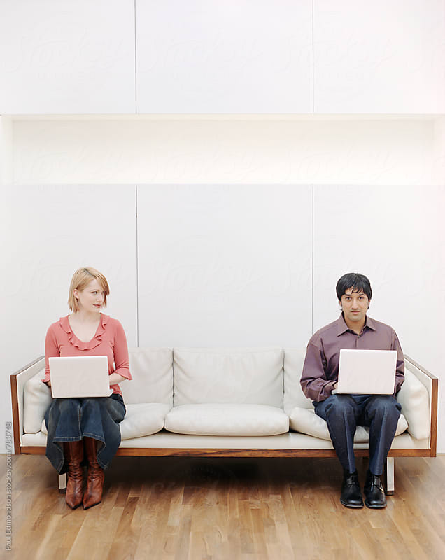 Attractive young couple sitting on modern couch, working on laptop comptures by Paul Edmondson for Stocksy United