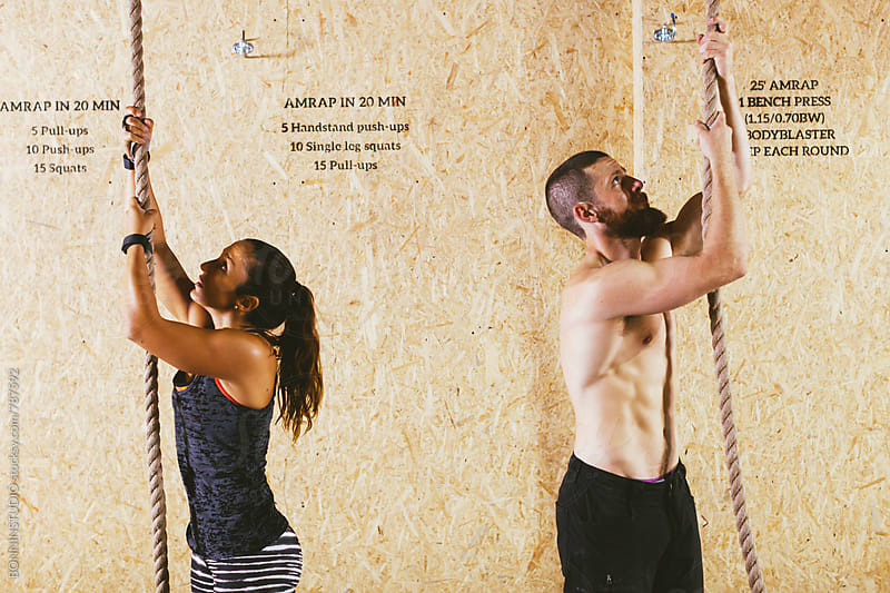 Couple climbing rope in a gym box. by BONNINSTUDIO for Stocksy United