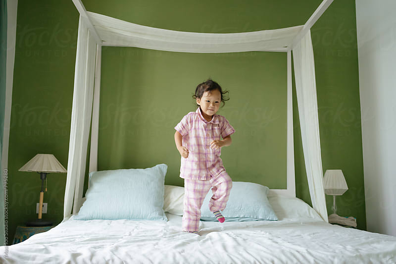 Cute toddler girl playing on bed by MaaHoo Studio for Stocksy United