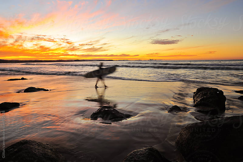 blurred surfer heading into the ocean at sunset by Gillian Vann for Stocksy United