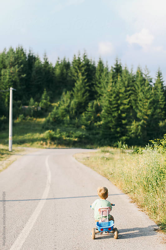 Kid on the road, from behind by Marija Kovac for Stocksy United