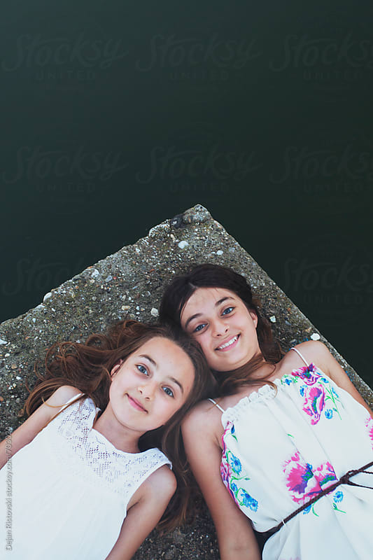 Girls lying on a dock.  by Dejan Ristovski for Stocksy United