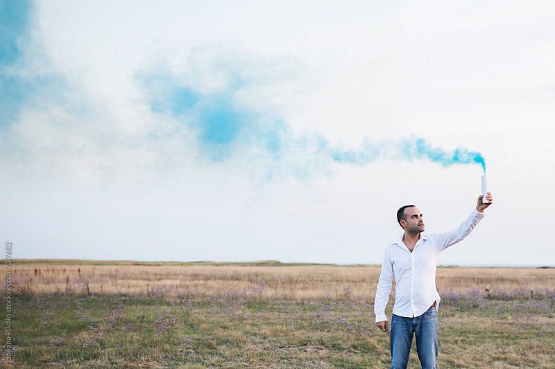 Man holding smoke bomb in nature by Jovana Rikalo for Stocksy United