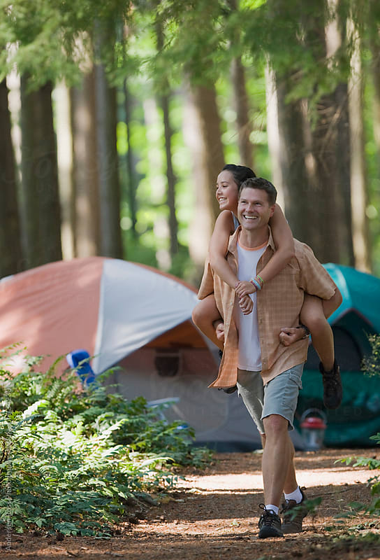 Father giving daughter (14-15) piggy back ride on campsite by Andersen Ross Photography for Stocksy United