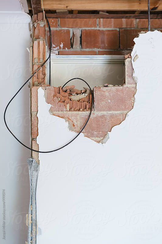 Partially demolished internal brick wall in house by Jacqui Miller for Stocksy United