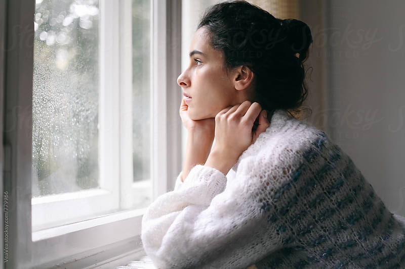 Beautiful brunette woman standing near a window during a rainy day by VeaVea for Stocksy United