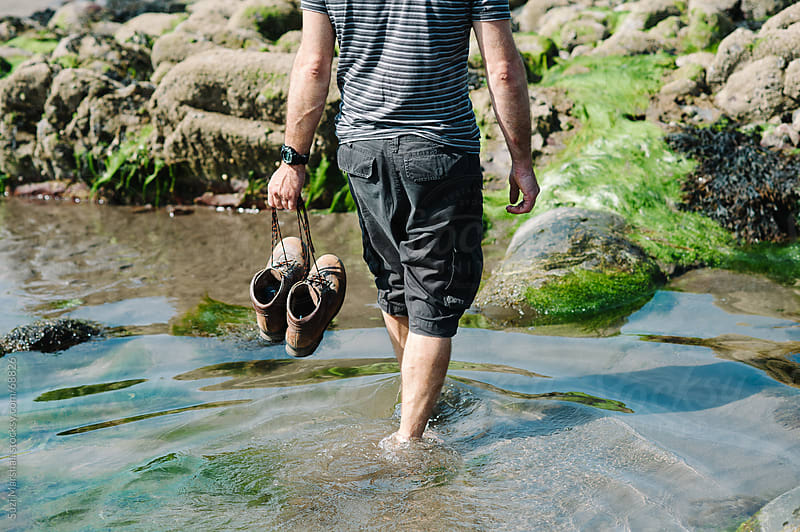 Man paddling in the sea holding his shoes by Suzi Marshall for Stocksy United