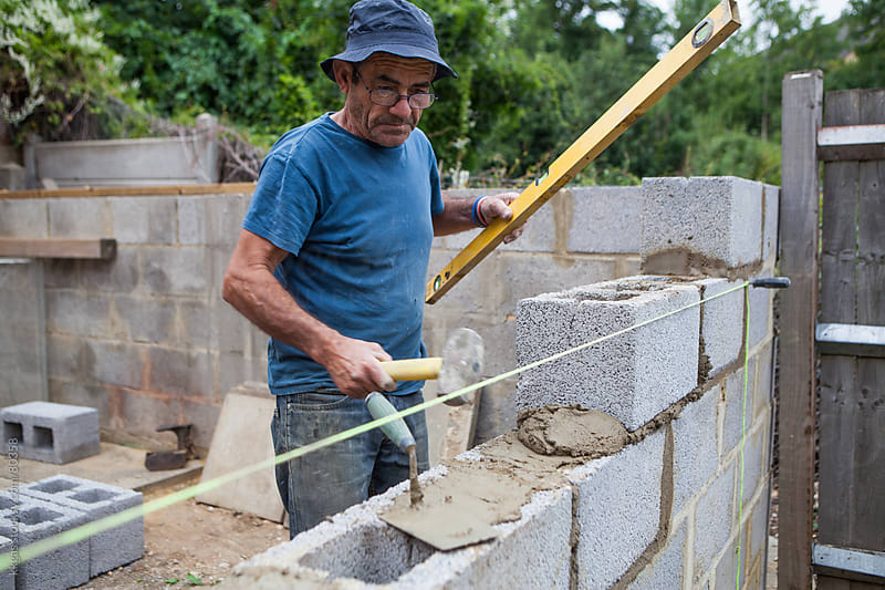 Builder working on a construction site building a wall by kkgas for Stocksy United