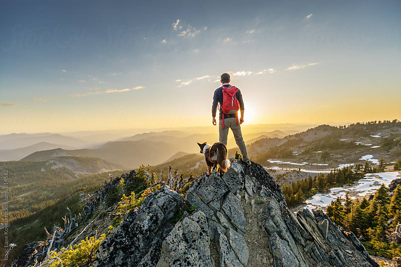 Man with dog standing on mountain top looking out towards sunset.  by Isaac Lane Koval for Stocksy United