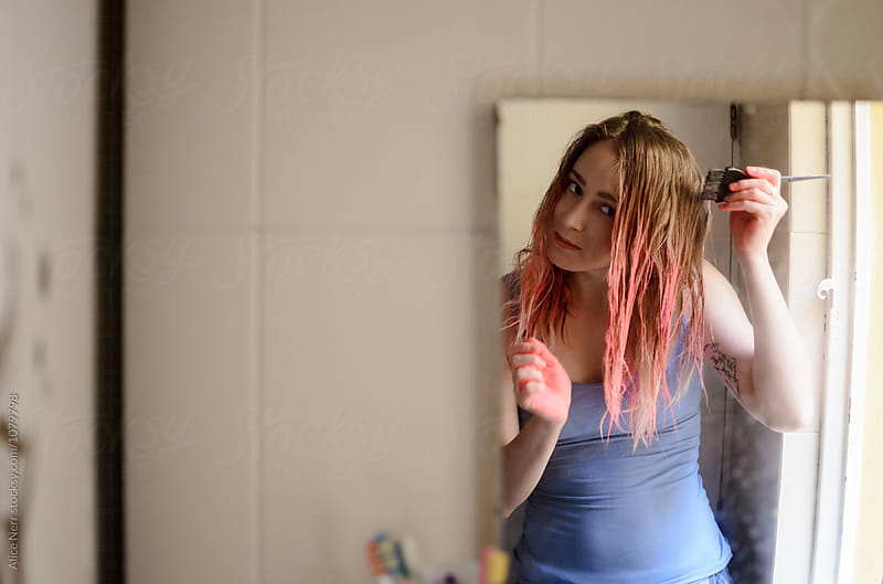 Reflection of a blond young female dying her hair pink in the bathroom by Alice Nerr for Stocksy United