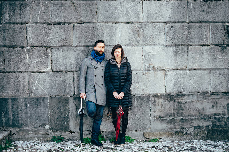 Beautiful Young Couple Portrait In Front Of a Grey Wall by HEX. for Stocksy United