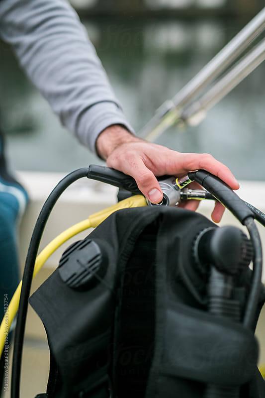 Hand on scuba diving equipment by Matthew Spaulding for Stocksy United