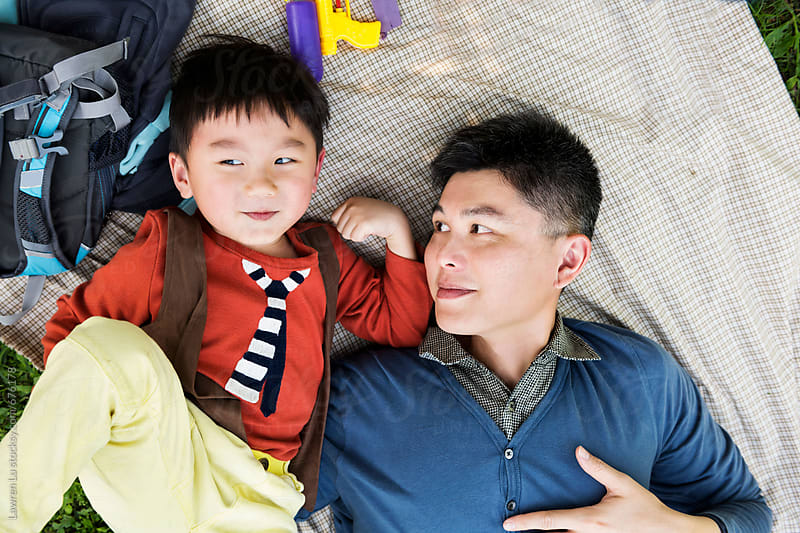 Kid and father lying on picnic blanket on green grass by Lawren Lu for Stocksy United