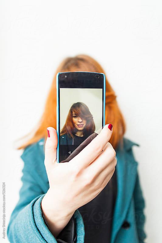 portrait of girl making selfie. by Audrey Shtecinjo for Stocksy United