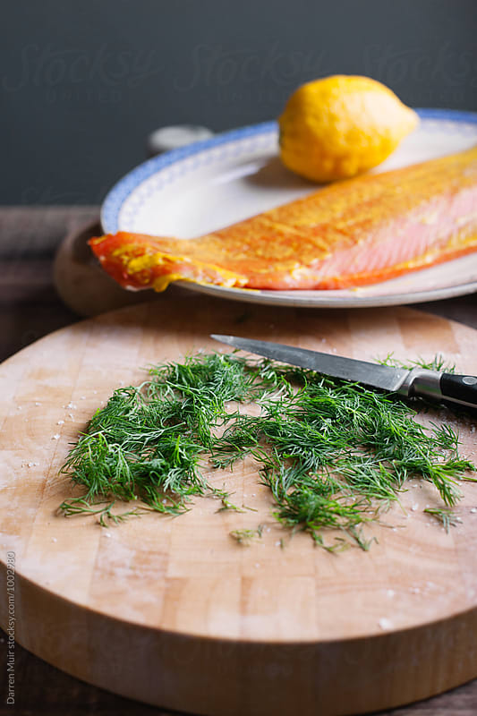 Series showing the making of salmon gravlax from start to finish. Dill on a cutting board. by Darren Muir for Stocksy United