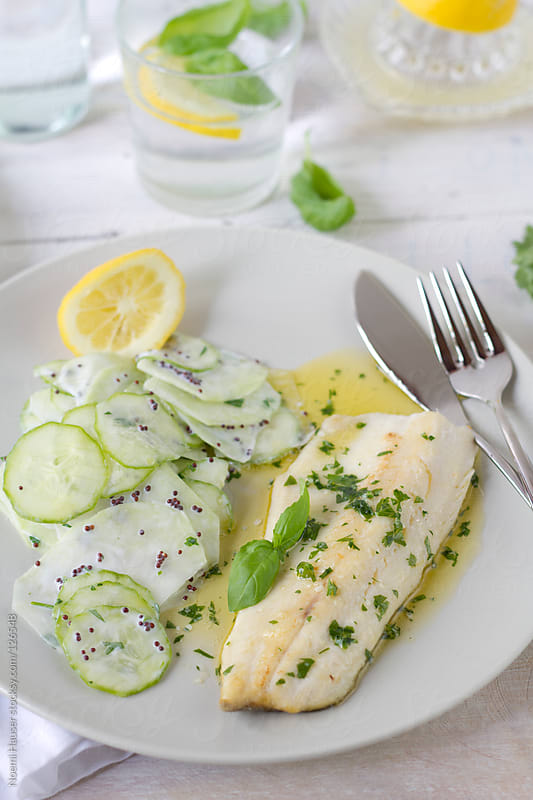 Trout with herb butter and cucumber-kohlrabi salad with mustard  by Noemi Hauser for Stocksy United