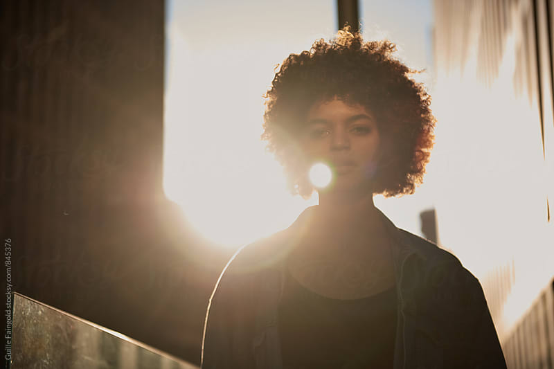 Portrait of young woman with afro looking at camera by Guille Faingold for Stocksy United