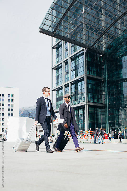 Two Businessmen Walking Side by Side in Front of Large Modern Glass Building by Julien L. Balmer for Stocksy United