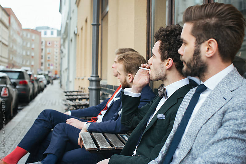 Stylish Young Man in Suit Sitting Outdoors with Friends and Smoking Cigarette by VISUALSPECTRUM for Stocksy United