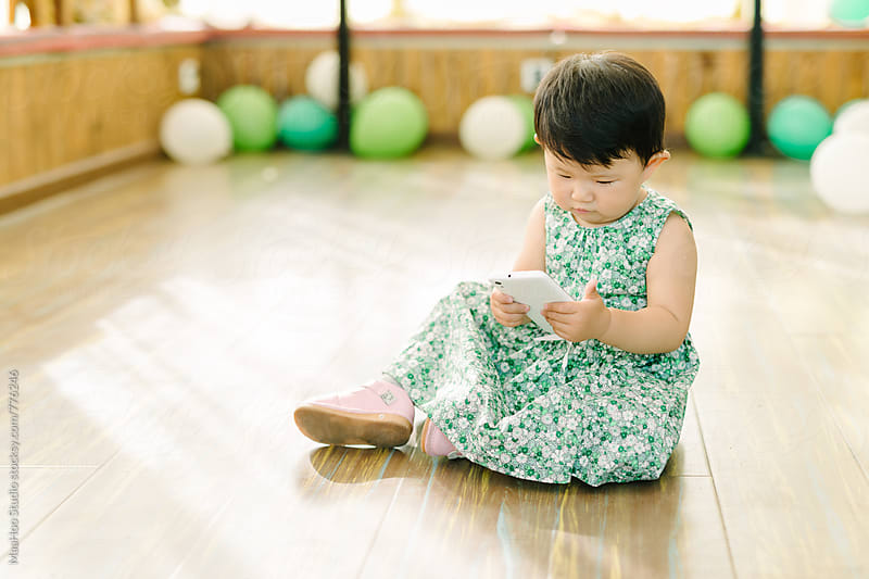 Toddler girl playing with cell phone on floor by MaaHoo Studio for Stocksy United