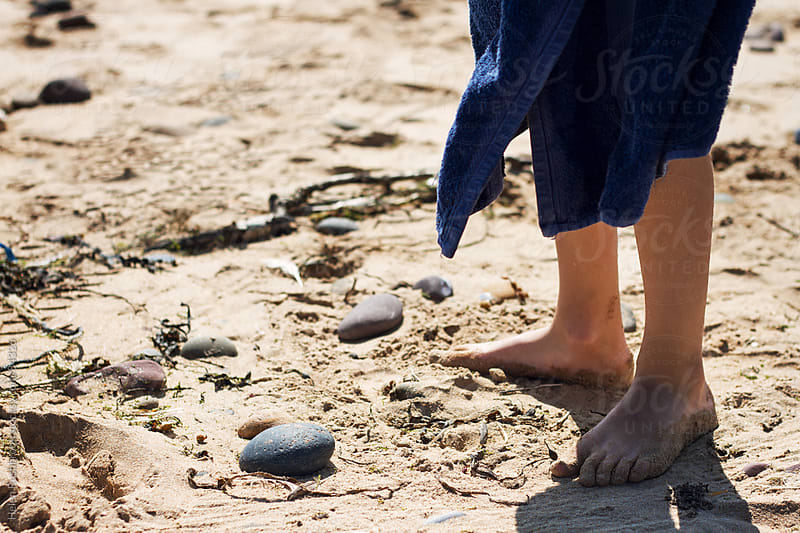 The towel-wrapped legs of a child on a beach. by Helen Rushbrook for Stocksy United