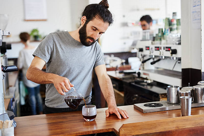 Barista pouring coffee from chemex in glass by Martí Sans for Stocksy United