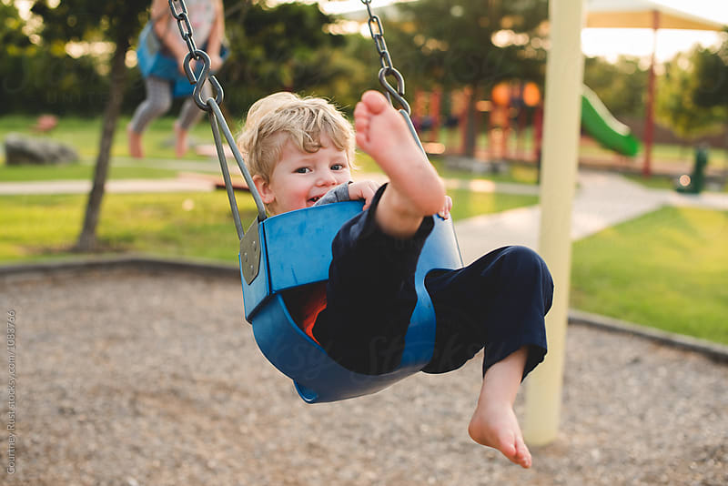 Boy kicking his foot on a swing by Courtney Rust for Stocksy United