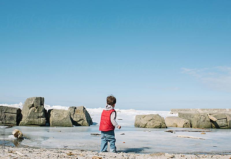Boy on Frozen Lake by Maria Manco for Stocksy United