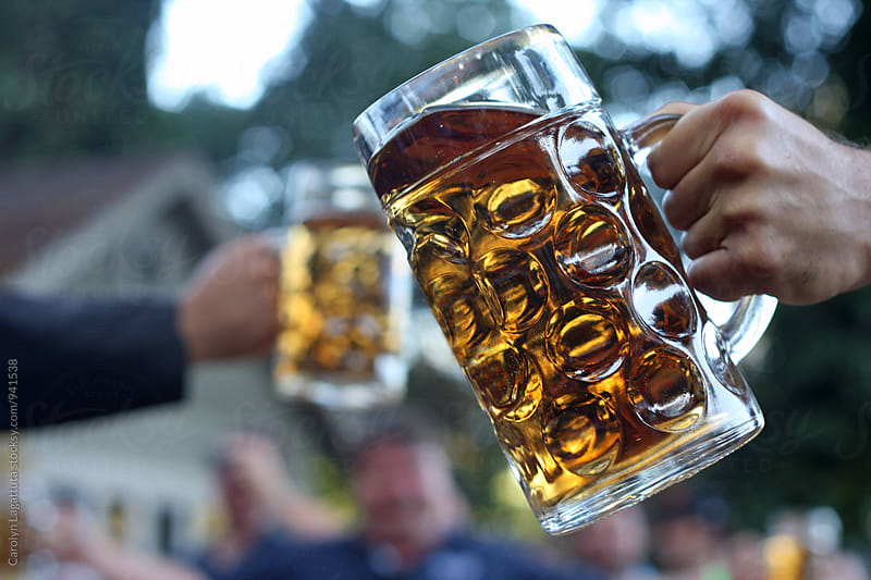 Men toasting beer with big, glass steins by Carolyn Lagattuta for Stocksy United