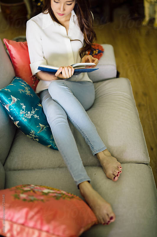A young beautiful woman, relaxing and reading at home by Alita Ong for Stocksy United