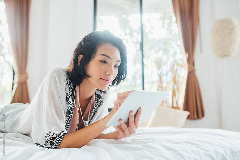 Woman Using a Tablet in Bed in the Morning by Lumina for Stocksy United