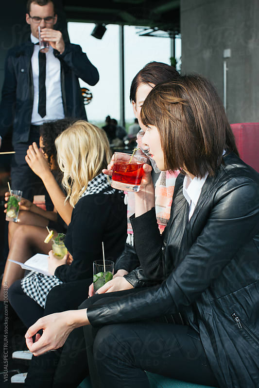 Group of Friends Having Drinks on Sunny Rooftop Bar by Julien L. Balmer for Stocksy United