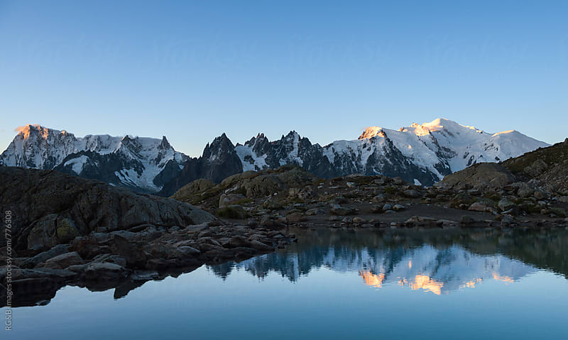 Sunrise over mountain peaks panorama reflected in the lake by RG&B Images for Stocksy United