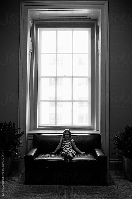A little girls sits below a very large window on a bench in a museum. by Kelsey Gerhard for Stocksy United