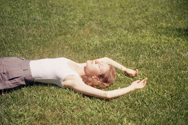A beautiful woman lying on the grass by Anna Malgina for Stocksy United
