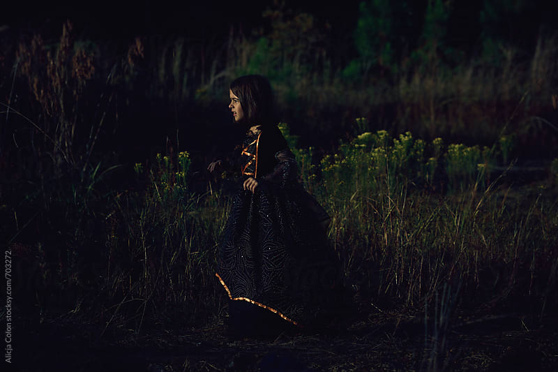 Young girl wearing a witch costume walking through woods by Alicja Colon for Stocksy United