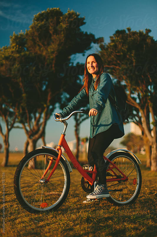 Beautiful girl riding her orange bicycle on the grass close to trees by Jonathan Caramanus for Stocksy United