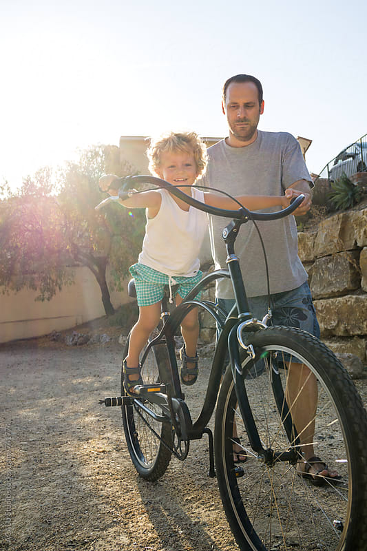 Little boy riding a bike with his father by ACALU Studio for Stocksy United