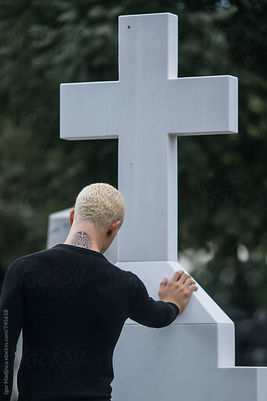 faith,blond young man with tattoo dressed in black in front of a white cross by Igor Madjinca for Stocksy United
